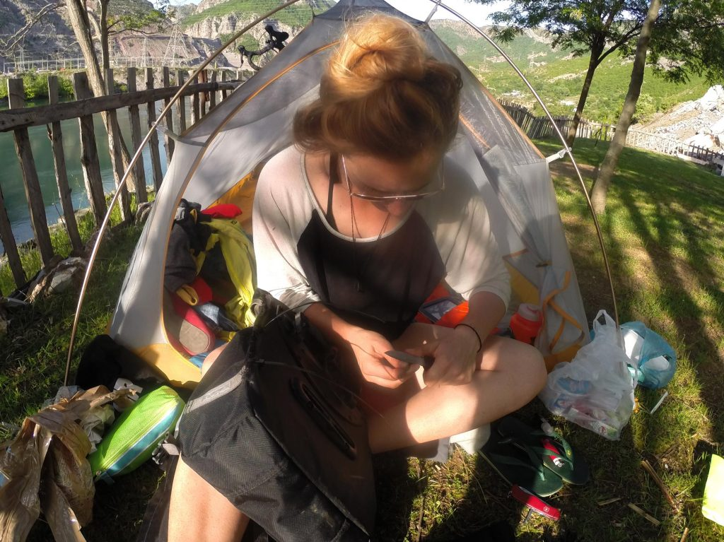 Sewing my pannier back together in rural Albania, at the base of a dam. We camped out in the yard of the owner of a tiny shop across the road.